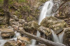 A waterfall flows after a rain in a hidden canyon on a mountain. A waterfall flows into a hidden canyon near a mountain top after heavy rainfall making, forming Royalty Free Stock Photography