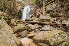 A waterfall flows after a rain in a hidden canyon on a mountain. A waterfall flows into a hidden canyon near a mountain top after heavy rainfall making, forming Stock Photos