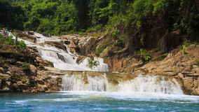 Waterfall flows among rocks falls into lake in tropical park stock video footage