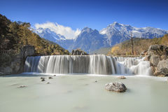Waterfall on foreground and Jade Dragon Snow Mountain on background - Yunnan, China Royalty Free Stock Images