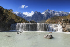 Waterfall on foreground and Jade Dragon Snow Mountain on background - Yunnan, China Royalty Free Stock Photo