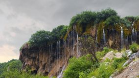 Waterfall in the forest flowing down from the rock stock footage