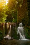 Waterfall in the forest with old wall background. Czerna town Poland stock image