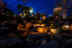 Waterfall fountain landscape at night with lights and tiki. Waterfall fountain landscape at night creates a beautiful soothing ambiance Stock Photo