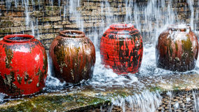Waterfall in the front garden with colorful water jar. Stock Image