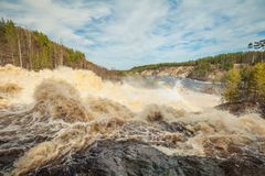 At the waterfall Girvas, Karelia. Russia. Arch of  rainbow over the water. Girvas eruptive crater. Spillway from hydroelectric power station. Spring time. Sunny Royalty Free Stock Photos