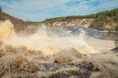 At the waterfall Girvas, Karelia. Russia. Spring. Girvas eruptive crater. Spillway from hydroelectric power station. Arch of  rainbow displaying the colours of Stock Photos