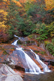 Waterfall in golden fall forest Stock Photos