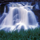 Waterfall with grass. A refreshing view of water cascading over rocks with grass in the foreground royalty free stock image