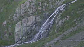 Waterfall in green Caucasus mountains ending into a mountain river. Waterfall in the Caucasus mountains ending into a mountain river stock video footage