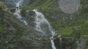 Waterfall in green rainforest in the Caucasus mountains ending into a mountain river. Waterfall in the Caucasus mountains surrounded by many pine trees, ending stock footage