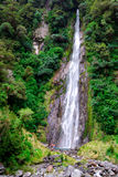 Waterfall in Haast pass. A very high waterfall in the Haast Pass - South Island, New Zealand Royalty Free Stock Photography