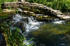 Waterfall In Hamilton New Jersey On A Beautiful Day. Waterfall flowing over the rocks at the Grounds For Sculpture in Hamilton New Jersey on a beautiful day royalty free stock image