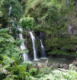 Waterfall on Hana Highway Maui Hawaii. One of the many waterfalls on the famous and picturesque Hana Highway, with lush vegetation and steep mountains. Tourists Stock Image
