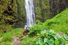 Waterfall on Hawaii. Man rest near waterfall Royalty Free Stock Image