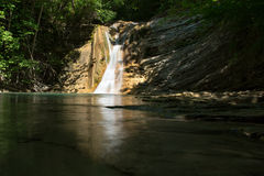 Waterfall hidden by the forest with slow shutter speed Stock Photography