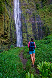 Waterfall hike person backpack paradise. Woman hikes up to beautiful large waterfall with backpack in hana maui, hawaii stock photography