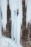 Waterfall Ice Climbing. A man ice climbing up a deep blue frozen waterfall using pick axes in the Rocky Mountains Royalty Free Stock Photo