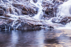 Waterfall. With icy rocks. clear water in the foreground reflecting some sunlight. Slow shutter speed royalty free stock photography