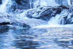 Waterfall. With icy rocks and a log. clear water in the foreground reflecting some sunlight. Slow shutter speed Royalty Free Stock Image