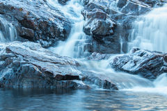 Waterfall. With icy rocks. In the shadows of a cloudy sky, clear water reflecting some light. Slow shutter speed stock photos