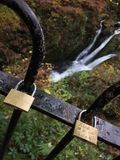 Waterfall-ing in love. A waterfall in the lake district slightly obstructed by a railing locked by lovers Stock Photography