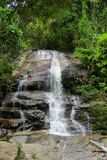 Waterfall in the jungle green forest on the rocks. Beautiful stream waterfall run on the rocks in the tropical jungle green forest. Scenic water fall between stock photography