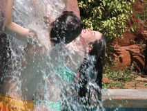 Waterfall Kids. Two children playing in the waterfall in a swimming pool Royalty Free Stock Images