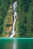 Waterfall on Konigsee lake. Landscape with a waterfall and a lake between mountains Stock Photos