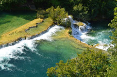 Waterfall of Krka River, Croatian National Park. Seen from high view point green river and waterfall cascade surrounded by green trees Royalty Free Stock Photos