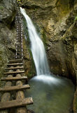 Waterfall with ladder in canyon Stock Photo