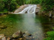 Waterfall with a lagoon on mountain stream Stock Photos