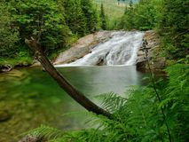 Waterfall with a lagoon on mountain stream Stock Images