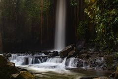 Waterfall landscape. Beautiful hidden Sumampan waterfall in tropical rainforest in Bali near Ubud. Slow shutter speed, motion stock images