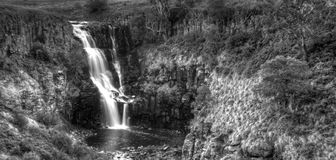 Waterfall landscape. A black and white photo of a waterfall cascading into a rock pool Stock Photo