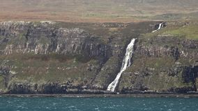 Waterfall on the left stopped and reversed by autumn storm Callum on the cliffs seen from Lower Milovaig - Isle of Skye. Scotland stock footage