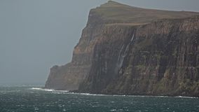 Waterfall on the left stopped and reversed by autumn storm Callum on the cliffs seen from Lower Milovaig - Isle of Skye. Scotland stock video footage