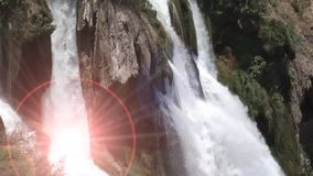 A waterfall with lens reflections in the water. A natural setting: A beautiful waterfall projecting clear reflections of multicolored lens in its waters that stock video