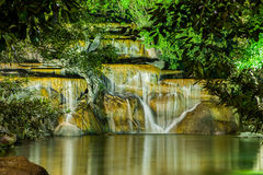 Waterfall with light from lamp in night garden. Chiang Rai Asian flower festival Thailand 2015 Royalty Free Stock Photo