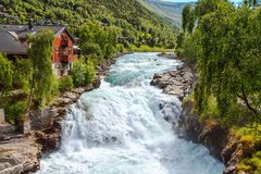 Waterfall and house in Lom, Norway. Waterfall in Lom, Norway - nature and travel background Stock Photo