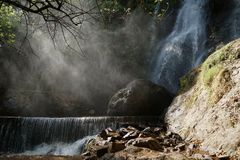 Waterfall and lower cascade in the forest with water fog lit with sunbeams.  Stock Image