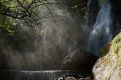 Waterfall and lower cascade in the forest with water fog lit with sunbeams.  Royalty Free Stock Photos