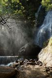Waterfall and lower cascade in the forest with water fog lit wit. H sunbeams Royalty Free Stock Photos