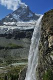 Waterfall and the Matterhorn. A waterfall in the Swiss alpine Zmutt valley in the foreground with the Matterhorn in the background.  Lakes on the valley floor Stock Photo