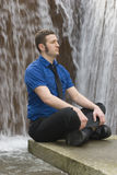 Waterfall meditation. A young business man finds his center Stock Image