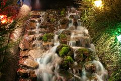 A waterfall on a minuature golf course at night. Lit up and beautiful at night Stock Photo