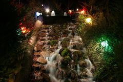 A waterfall on a minuature golf course at night. Lit up and beautiful at night Stock Images