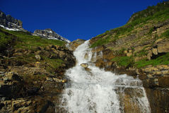 Waterfall, Montana. Waterfall, snow mountains and intense blue, sky, near Logan Pass, Glacier National Park, Montana Royalty Free Stock Image