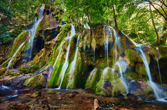Waterfall on mossy boulders. With long exposure Stock Photography