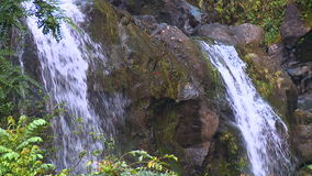 Waterfall on mossy rock cliff stock video footage